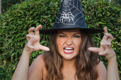 Young witch in black hat screaming at the camera Stock Photo