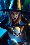 Young Witch Is Cooking Skull Potion. Young witch with awfully face looking at camera and tells evil words. She is holds skull above cauldron with poison potion royalty free stock photo