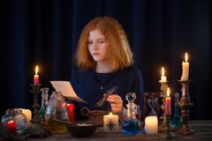 Young witch is engaged in witchcraft stock photos