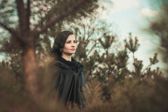 Young witch in a forest Stock Images