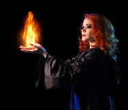 Young witch girl holds fire isolated Royalty Free Stock Images