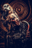 Young  witch hloding sickle. Bright make up, skull, smoke-  halloween theme. Royalty Free Stock Photography