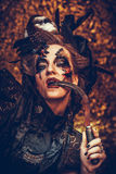Young  witch hloding sickle. Bright make up, skull, smoke-  halloween theme. Royalty Free Stock Images