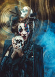 Young  witch hloding skull. Bright make up and  smoke-  halloween theme. Stock Image