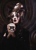 Young  witch hloding skull. Bright make up and  smoke-  halloween theme. Stock Images