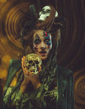 Young  witch hloding skull. Bright make up and  smoke-  halloween theme. Stock Photography
