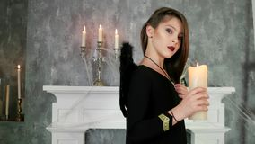 Young witch holding candle, halloween party celebration, girl wearing dark angels costume, evil stock video footage