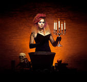 Young witch making witchcraft on a Halloween background Royalty Free Stock Photos
