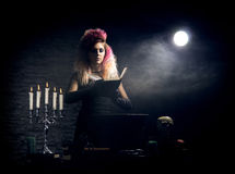 Young witch making witchcraft on a Halloween background. Beautiful witch making the witchcraft over the smoky background. Halloween image Stock Photography
