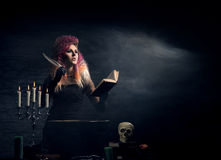 Young witch making witchcraft on a Halloween background. Beautiful witch making the witchcraft over the smoky background. Halloween image Stock Photo
