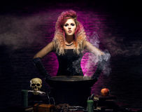 Young witch making witchcraft in a Hallowen dungeon. Young and beautiful witch in a dungeon. Halloween concept Stock Image