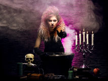 Young witch making witchcraft in a Hallowen dungeon. Young and beautiful witch in a dungeon. Halloween concept Royalty Free Stock Photo