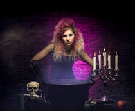 Young witch making witchcraft in a Hallowen dungeon. Young and beautiful witch in a dungeon. Halloween concept Stock Images