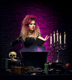 Young witch making witchcraft in a Hallowen dungeon. Young and beautiful witch in a dungeon. Halloween concept Royalty Free Stock Photos