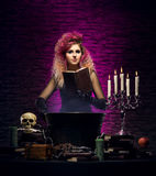 Young witch making witchcraft in a Hallowen dungeon. Young and beautiful witch in a dungeon. Halloween concept Stock Photos