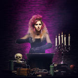 Young witch making witchcraft in a Hallowen dungeon. Young and beautiful witch in a dungeon. Halloween concept Royalty Free Stock Photography