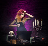 Young witch making witchcraft in a Hallowen dungeon. Young and beautiful witch in a dungeon. Halloween concept Royalty Free Stock Image