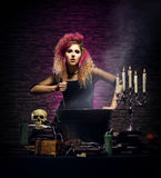 Young witch making witchcraft in a Hallowen dungeon. Young and beautiful witch in a dungeon. Halloween concept Stock Photo
