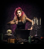 Young witch making witchcraft in a Hallowen dungeon. Young and beautiful witch in a dungeon. Halloween concept Stock Photography