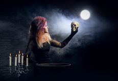 Young witch making witchcraft in a Hallowen dungeon. Beautiful witch making the witchcraft over the smoky background. Halloween image Royalty Free Stock Images