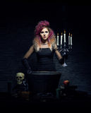 Young witch making witchcraft in a Hallowen dungeon. Beautiful witch making the witchcraft over the smoky background. Halloween image Royalty Free Stock Image