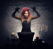 Young witch making witchcraft in a Hallowen dungeon. Beautiful witch making the witchcraft over the smoky background. Halloween image Royalty Free Stock Photos