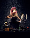 Young witch making witchcraft in a Hallowen dungeon. Beautiful witch making the witchcraft over the smoky background. Halloween image Stock Photos
