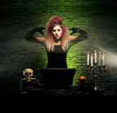 Young witch making witchcraft in a Hallowen dungeon. Beautiful witch making the witchcraft over the smoky background. Halloween image Royalty Free Stock Photo