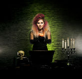 Young witch making witchcraft in a Hallowen dungeon. Beautiful witch making the witchcraft over the smoky background. Halloween image Stock Images