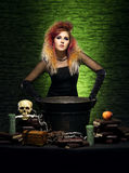 Young witch making witchcraft in a Hallowen dungeon. Beautiful witch making the witchcraft over the smoky background. Halloween image Royalty Free Stock Photography