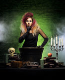 Young witch making witchcraft in a Hallowen dungeon Royalty Free Stock Photos