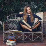 Young witch practicing with magic books. Helloween. Pretty young witch student of magic school practicing with magic books outdoors. Helloween Royalty Free Stock Photos