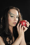 Young witch with red apple. Young witch holdin red apple Royalty Free Stock Image