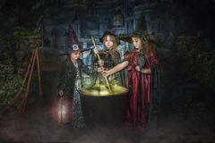 Young witches stirring cauldron Stock Photo