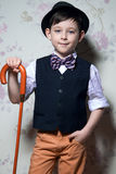 A young wizard with brown cane. A boy is wearing a light shirt. With black waistcoat. The hat and striped bow tie complete his look. Studio shot Royalty Free Stock Images
