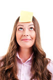 Young woma with yellow sticky note. On forehead Stock Photography