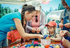 Young woman – volunteer explaining how to knit colorful table napkin Stock Photo