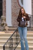 Young Woman 10. Young woman in front of mansion looking for something in her purse Stock Photo