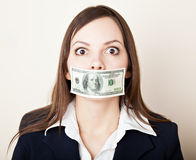 Young woman with 100 dollars on her mouth. Young brunette woman with 100 dollars on her mouth royalty free stock photography