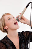Young woman. Young fun and bubbly woman sings into microphone stock photography