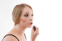 Young woman. Applies make-up lipstick beautiful skin royalty free stock photography