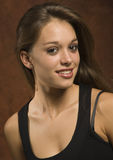 Young woman. Pretty young woman against a brown background stock photo