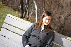 Young Woman. A beautiful young woman sitting on a bench Stock Images