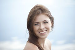 Young woman. Smiling cute young woman on cloudy sky background Royalty Free Stock Images