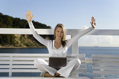 Young woman. With a laptop on the pier stock photography
