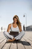 Young woman. With a laptop on the pier Stock Images