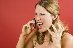 Young Woman. On red looking angry on cell phone Royalty Free Stock Photography