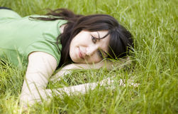 Young woman. Sitting  on the  grass on a spring   sunny day Royalty Free Stock Image