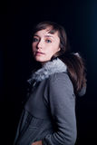 Young woman. A young woman on a plain black background wearing a gray fur lined hoodie and striped dress Royalty Free Stock Photos