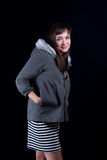 Young woman. A young woman on a plain black background wearing a gray fur lined hoodie and striped dress Stock Photo